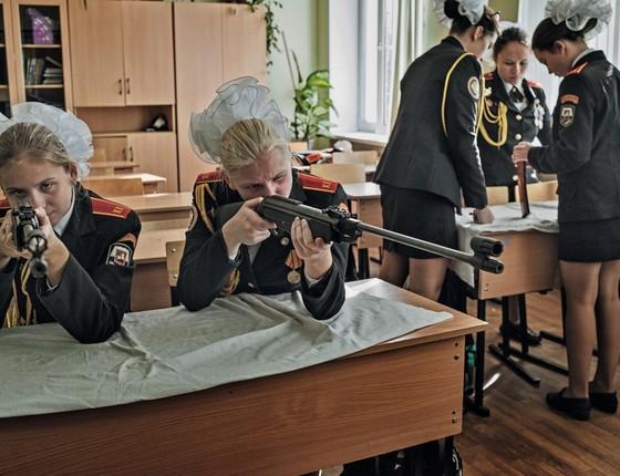 Garotas aprendem a montar, carregar e atirar com rifles numa escola para cadetes em Moscou. A cultura militar é exaltada entre parte da juventude russa (Foto: Yuri Kozyrev / NOOR)