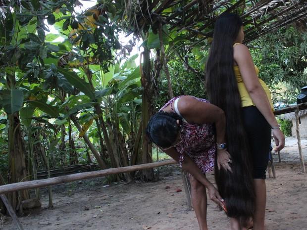 A jovem conta com a ajuda da mãe para os cuidados diários com as enormes madeixas (Foto: Patrícia Andrade/G1)