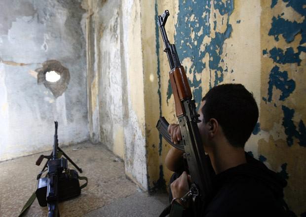 Integrante do Hezbollah se posiciona em telhado de prédio em bairro xiita de Beirute, capital do Líbano, nesta segunda-feira (22) (Foto: AP)