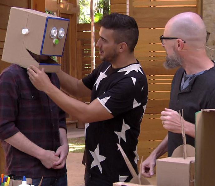 Tiago experimenta a cabeça de papelão de um boneco (Foto: TV Globo)