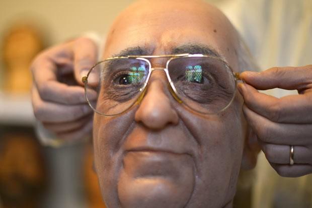 Fernando Canini, diretor do museu, coloca óculos no boneco de cera de Francisco (Foto: Gabriel Bouys/AFP)