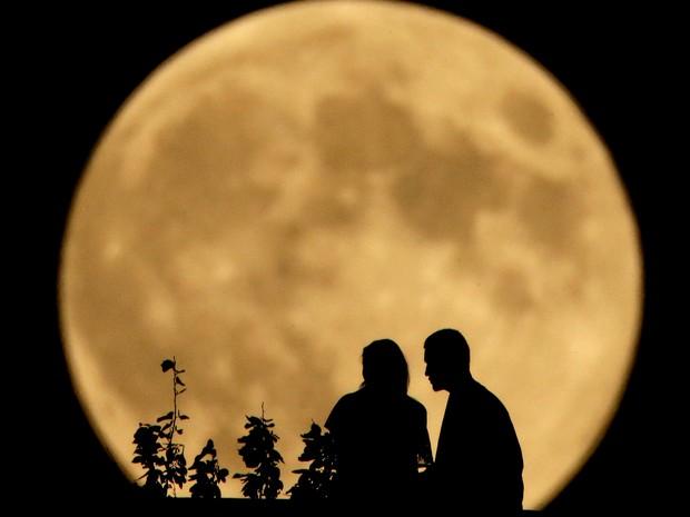 -HN- Um casal é visto com a lua cheia ao fundo em Kansas, nos EUA (Foto: Charlie Riedel/AP)