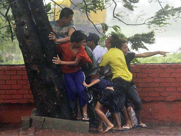 Adultos e adolescentes tentam se proteger dos ventos do tufão segurando em uma árvore na capital Manila. (Foto: Romeo Ranoco / Reuters)