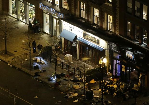 Investigadores analisam o local em que aconteceu uma das explosoões durante a Maratona de Boston, nos Estados Unidos (Foto: Elise Amendola/AP)
