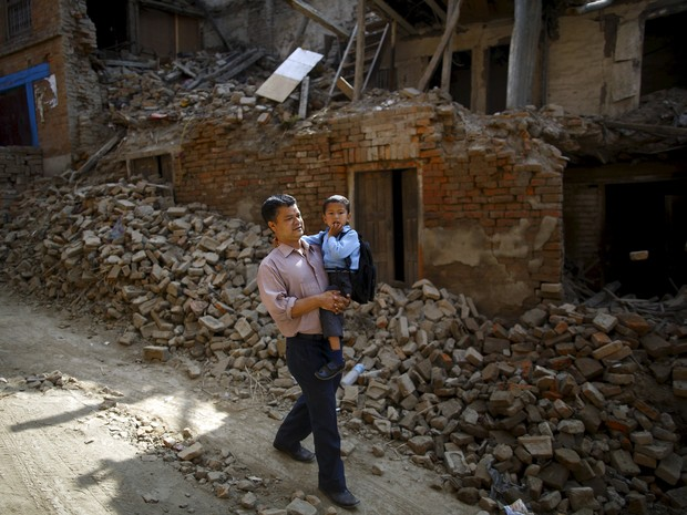 Birendra Karmacharya carrega seu filho de 4 anos rumo ao primeiro dia de aulas após o terremoto que destruiu o Nepal (Foto: Reuters/Navesh Chitrakar)