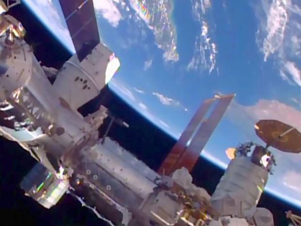 Imagem da Nasa TV mostra a cápsula Dragon da SpaceX na Estação Espacial Internacional neste domingo (10) (Foto: Nasa/AFP)