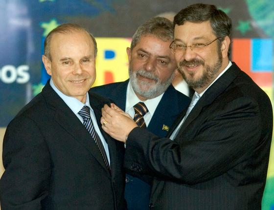 O ex-ministro da Fazenda, Antonio Palocci (d), acompanhado de Lula (c), coloca broche do ministério da Fazenda no novo ministro, Guido Mantega (Foto:  ED FERREIRA/ESTADÃO CONTEÚDO)