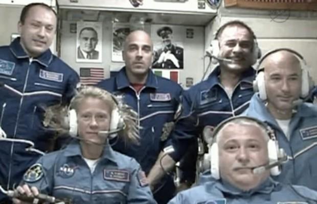 Três novos tripulantes levados pela Souyz à ISS (macacão azul claro) dão entrevista coletiva ao lado de outros três astronautas que já estavam na Estação. (Foto: Reprodução/Nasa)