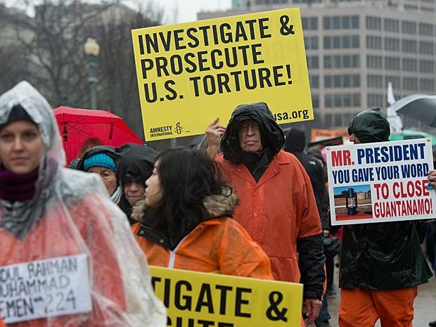 'Investiguem e processem a tortura dos EUA', diz cartaz exibido no protesto (Foto: Nicholas Kamm/AFP)