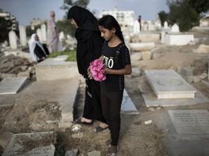 Mulher palestina e menina levam flores em um túmulo da família no feriado do fim do Ramadã (Eid al-Fitr) em Gaza.  (Foto: Reuters/Finbarr O'Reilly)