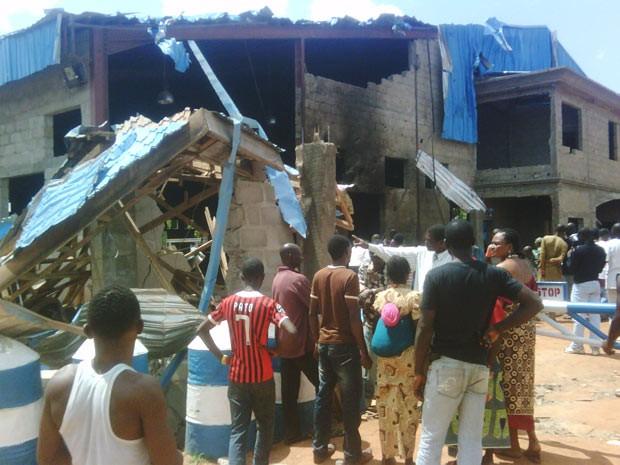 Moradores observam igreja parcialmente destruída em Kaduna, na Nigéria, após ataque suicida neste domingo (17) (Foto: Victor Ulasi / AFP)