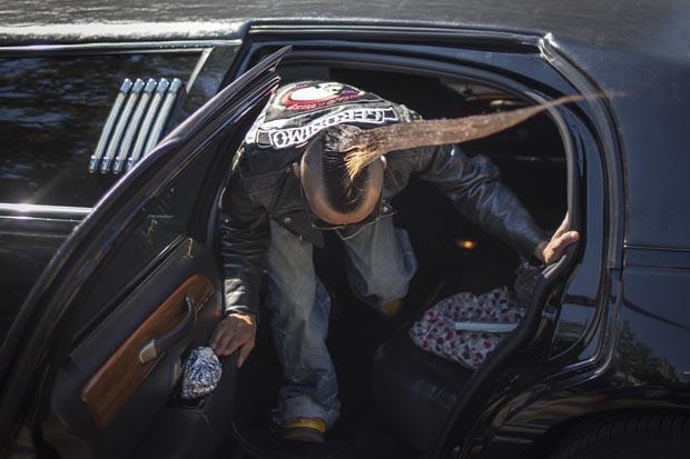 O japonês tenta sair do carro sem desmanchar o penteado (Foto: Adrees Latif/Reuters)