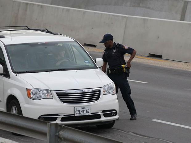 Policial checa documentos de motorista em frente ao portão do Forte Hood, no Texas, apó o alerta devido ao tiroteio na base militar (Foto: Deborah Cannon/Austin American-Statesman/AP)