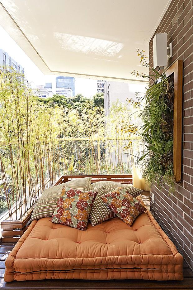 No projeto da paisagista Paula Magaldi para esta varanda, o tatame, feito de deque de cumaru, recebe o futon e as almofadas para compor o espaço destinado ao descanso. Atrás dele, na esquina da varanda, a floreira canelada forma o L, onde ficam os bambus altos, que garantem a privacidade dos moradores (Foto: Lilian Knobel/Casa e Jardim)