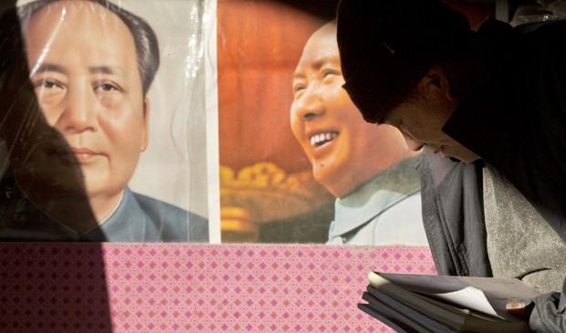 Vendedor de livros organiza os produtos perto de cartazes de Mao em Pequim no 120º aniversário do líder da China socialista. (Foto: Alexander F. Yuan/AP)