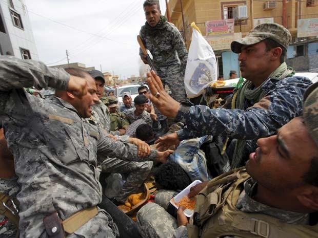 Membro das forças de segurança do Iraque bate em insurgente do Estado Islâmico que foi capturado em Tikrit nesta quarta-feira (1º) (Foto: REUTERS/Alaa Al-Marjani )