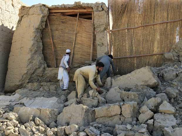Homens afegãos trabalham em uma casa no distrito de Behsud, província de Nangarhar, no Afeganistão (Foto: Parwiz / Reuters)