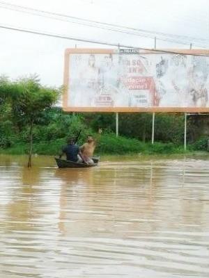 Morador de Juazeiro do Norte se locomove em canoa por ruas alagadas (Foto: Agência Miséria)