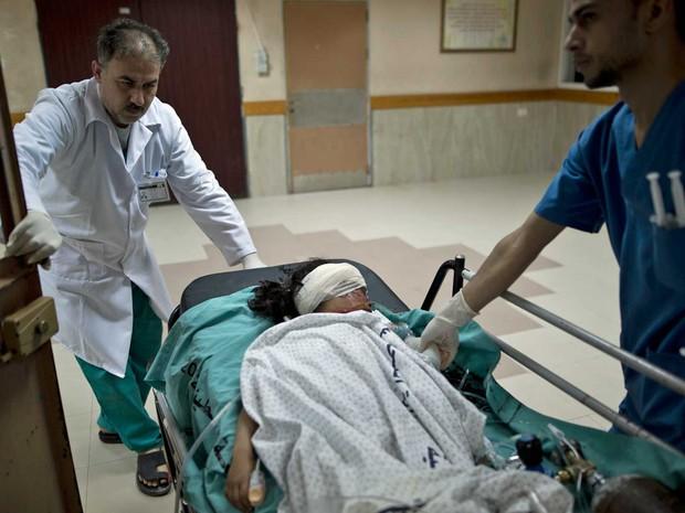 Médicos palestinos tratam da menina Israa Abu Khussa, de 6 anos, ferida após bombardeio de Israel na Faixa de gaza (Foto: AFP Photo)