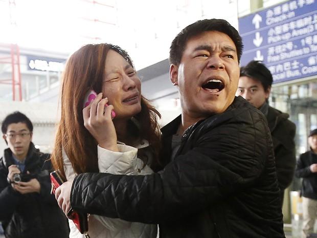 Parente de passageiro do voo MH370 da Malaysia Airlines chora enquanto fala no celular no Aeroporto Internacional de Pequim, China, neste sábado (8). O voo que ia de Kuala Lumpur a Pequim, na China, está desaparecido. Aeronave levava 239 pessoas a bordo. (Foto: Kim Kyung-Hoon/Reuters)