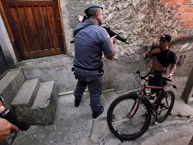 Policial fiscaliza morador durante operação na favela de Paraisópolis, na zona sul de São Paulo. (Foto: Nacho Doce/Reuters)