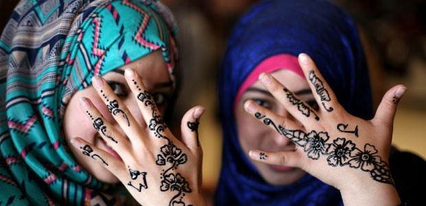 Palestinas mostram mãos pintadas com hena na Cidade de Gaza, em março de 2014 (Foto: Mohammed Abed/AFP)