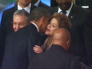 Logo após apertar a mão de Raúl Castro, o presidente americano, Barack Obama, cumprimenta com um beijo a presidente Dilma Rousseff (Foto: AP/SABC)