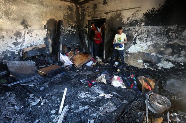 Palestinos olham estragos causados após incêndio em casa na Cisjordânia nesta quinta-feira (30); um bebê morreu (Foto: Jaafar Ashtiyeh/AFP)