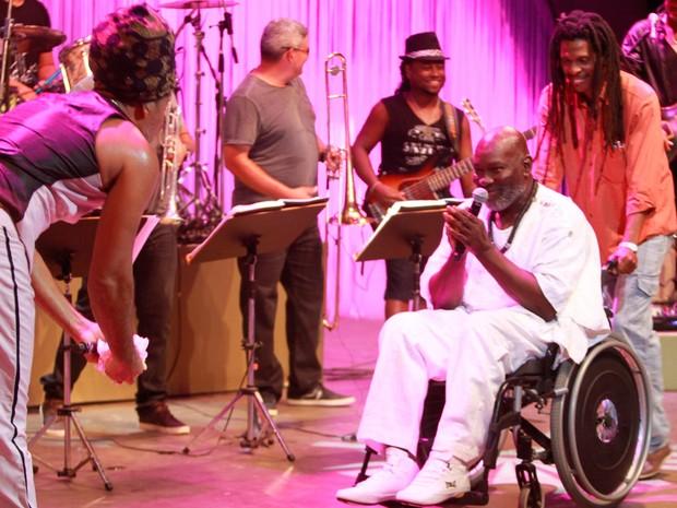 Na cadeira de rodas por problema de saúde, Lazzo Matumbi é recebido no palco por Carlinhos Brown (Foto: Carol Garcia/GOVBA)