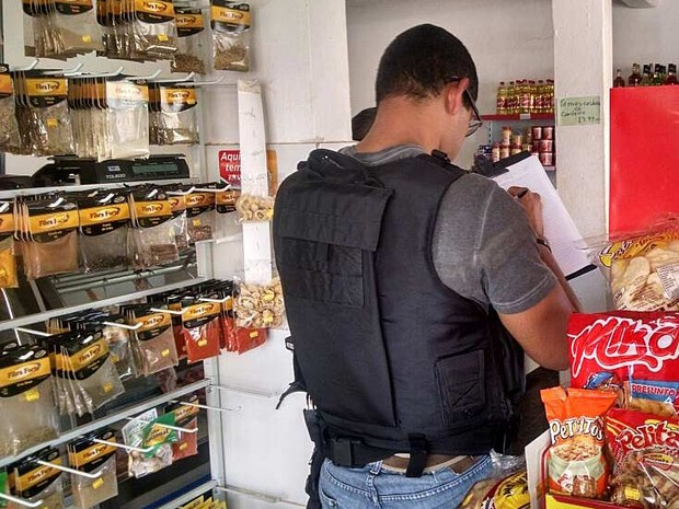 Policial na mercearia em frente da qual ocorreu o assasinato de homem que segurava filho de 1 ano e 2 meses; criança foi atingida por 3 tiros (Foto: Fernando Caixeta/G1)