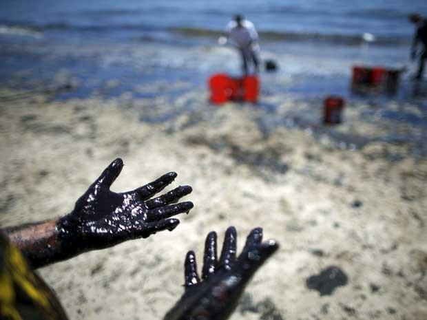 Homem mostra mãos sujas de óleo durante limpeza de praia na califórnia. (Foto: Lucy Nicholson / Reuters)