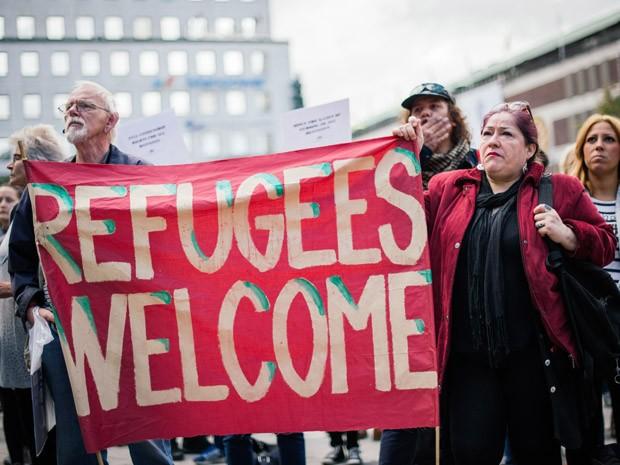Participante de manifestação pró-migrante em Estocolmo, na Suécia, neste sábado (Foto: AFP PHOTO/JONATHAN NACKSTRAND)