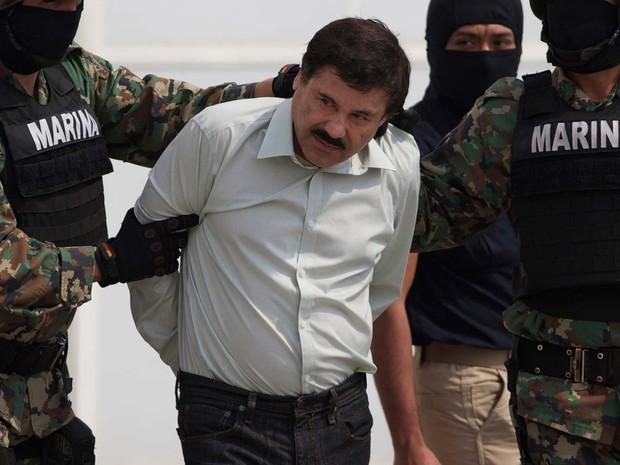 Imagem de 22 de fevereiro de 2014 mostra Joaquín El Chapo Gúzman sendo escoltado por fuzileiros navais até um helicóptero na Cidade do México (Foto: AP Photo/Eduardo Verdugo, File )