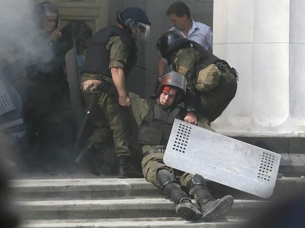 Membro da guarda nacional ferido é arrastado por colegas em frente ao prédio do Parlamento da Ucrânia, em Kiev. Dezenas de pessoas ficaram feridas após explosões de artefatos atirados por manifestantes, segundo o ministro do Interior do país (Foto: Valentyn Ogirenko/Reuters)