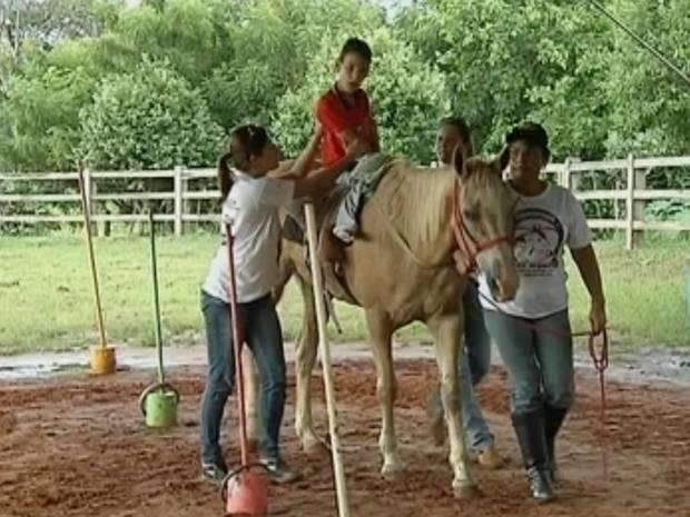 Paciente durante tratamento com cavalos em Fernandópolis (Foto: Reprodução/ TV TEM)