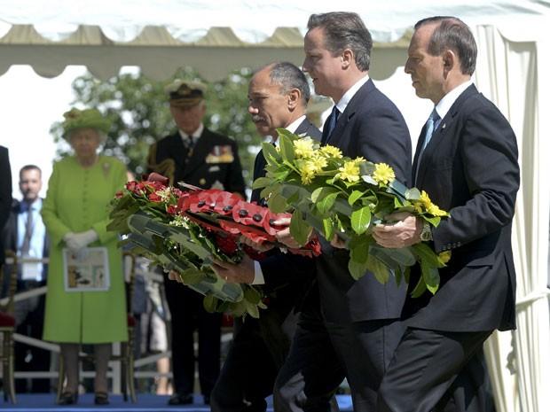 Da esquerda para a direita: o governador-geral da Nova Zelândia, Jerry Mateparae, o premiê britânico, David Cameron, e o primeiro-ministro da Austrália, Tony Abbott, durante cerimônia em Bayeux, na França. Ao fundo, de verde, a Rainha Elizabeth. (Foto: Thomas Bregardis/Reuters)