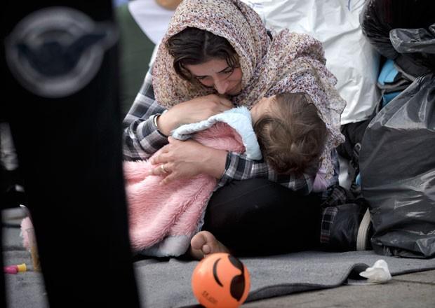 Mulher imigrante chora enquanto segura um bebê em Atenas, na Grécia, na segunda-feira (29) (Foto: Vadim Ghirda/AP)