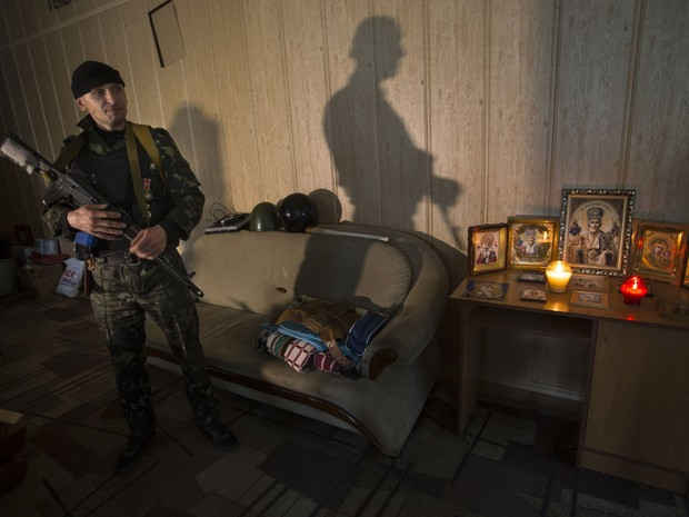 Soldado russo toma prédio da Promotoria de Luhansk, na Ucrânia (Foto: Alexander Zemlianichenko/AP)