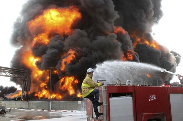 Bombeiro palestino tenta conter fogo em incêndio na única central elétrica de Gaza, atingida por um bombardeio de Israel nesta terça-feira (29) (Foto: Ahmed Zakot/Reuters)