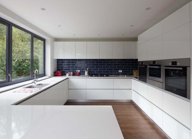 A cozinha ganhou revestimento azul na parede. Repare nas enormes janelas emolduradas por aço steel-frame  (Foto: Divulgação/Nick Leith-Smith Architecture+Design)
