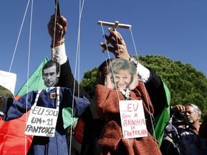 Manifestantes seguram fantoches representando o primeiro-ministro de Portugal, Pedro Passos Coelho, e a chanceler da Alemanha, Angela Merkel, nesta segunda-feira (12) em Lisboa (Foto: AFP)