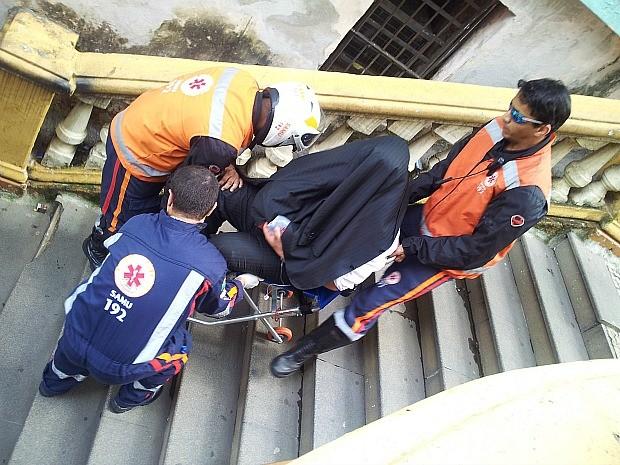 Defensor público detido passa mal e sai carregado por paramédicos com paletó na cabeça para esconder rosto. (Foto: Juirana Nobres/ G1)