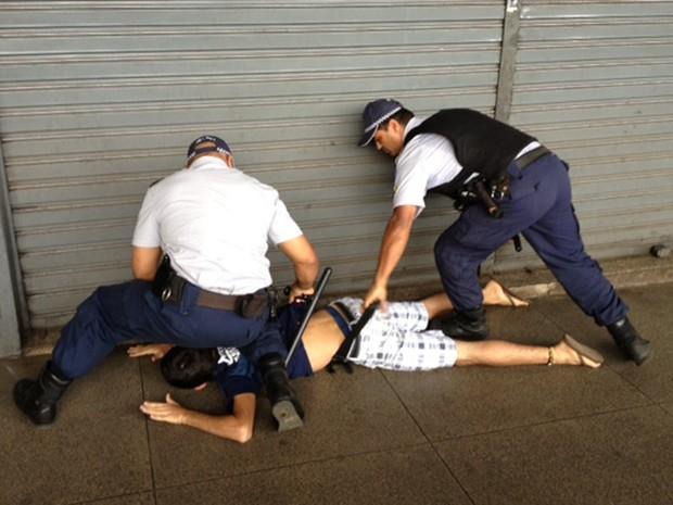 Manifestante é imobilizado por policiais na rodoviária do Plano Piloto, em Brasília. Ele foi revistado e em seguida liberado (Foto: Fabiano Costa/G1)