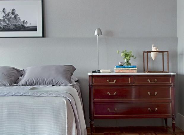 Um extenso painel de madeira faz as vezes de cabeceira da cama, com papel da Orlean, assim como a parede. A cômoda antiga serve de criado-mudo e abriga escultura do Gabinete Duilio Sartori (Foto: Denilson Machado / MCA Estúdio / Divulgação)