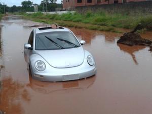 Mulher atola carro em poça e fica ilhada em bairro de Campo Grande (Foto: Chico Gomes/TV Morena)
