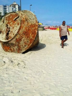 Curiosos tentam identificar objeto que surgiu nas areias de Praia Grande, SP. (Foto: Andressa Amorim/G1)