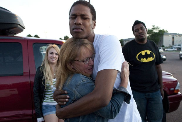 Mãe de vítima abraça amigo de seu filho após o ataque desta sexta-feira (20) (Foto: AP)