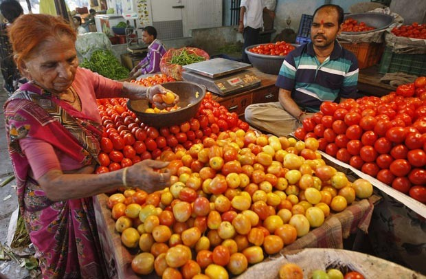 Mulher escolhe tomates em mercado na cidade de  Ahmedabad, na Índia. (Foto: Reuters/Amit Dave)