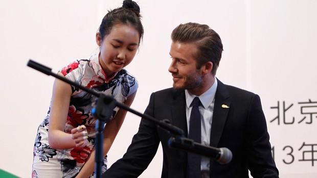 David Beckham ao lado de uma estudante aprendendo um instrumento chinês tradicional (Foto: Agência Reuters)