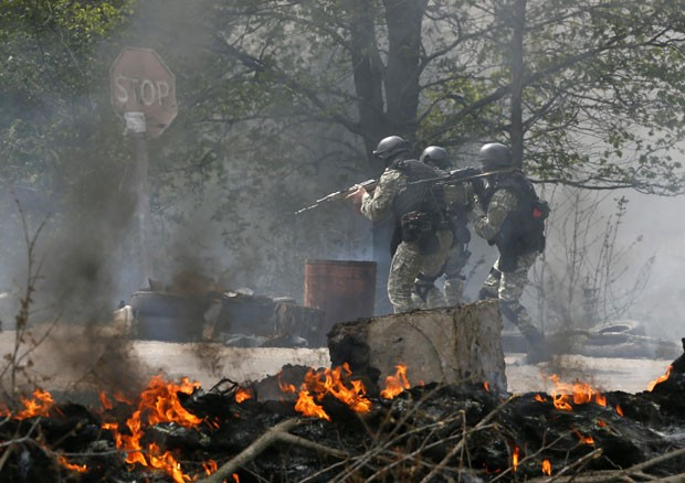 Forças de segurança ucranianas passam por posto de controle de separatistas destruído em Slaviansk nesta quinta-feira (24); cinco ativistas pró-Rússia morreram em combates (Foto: Gleb Garanich/Reuters)